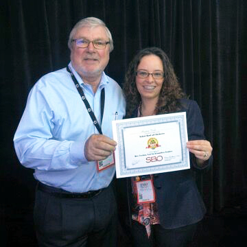 Business Development Manager for Music Sales, Ian Morgan, and MusicFirst Western Accounts Manager, Jenny Amaya, accepting the School Band and Orchestra Best Tools for Schools Award